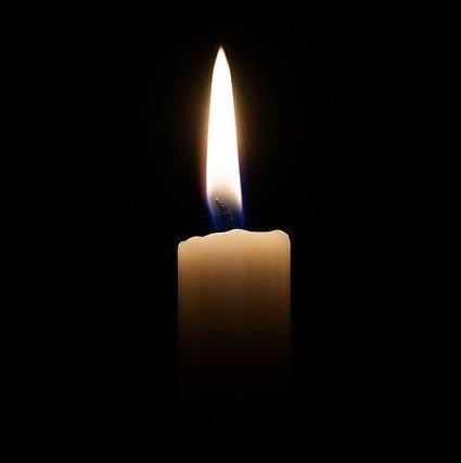 Płonące świeca na czarnym tle, jako znak żałoby.